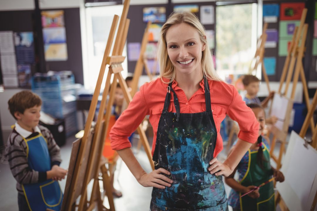 Portrait of smiling teacher standing with hands on hip in drawing class Free Stock Images from PikWizard