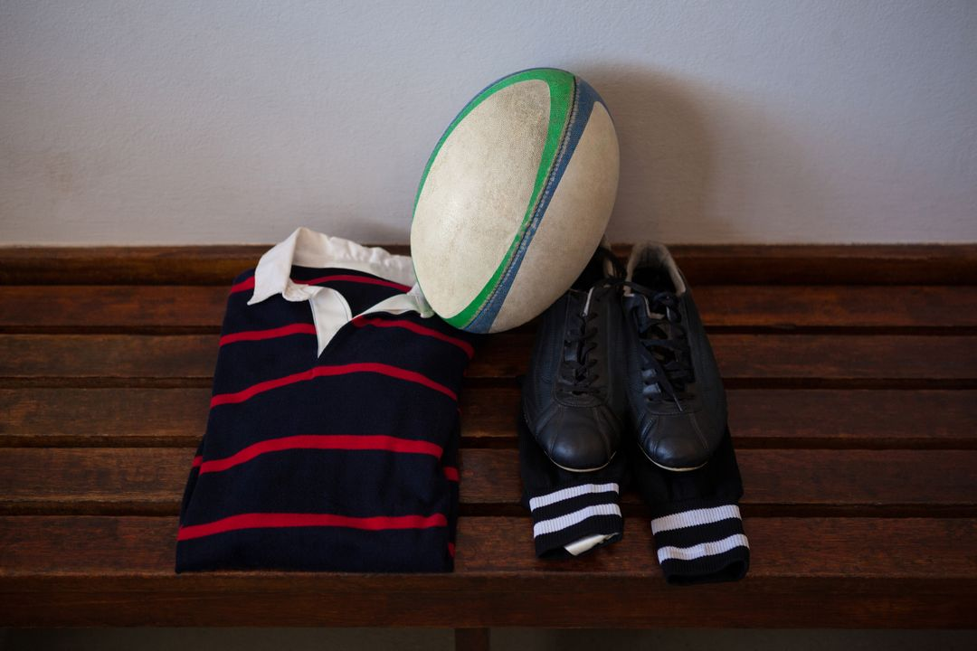 High angle view of rugby ball and clothes with shoes on bench in locker room Free Stock Images from PikWizard