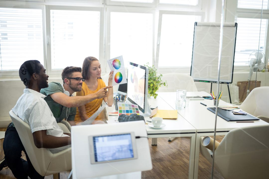Graphic designers discussing over computer at their desk in office