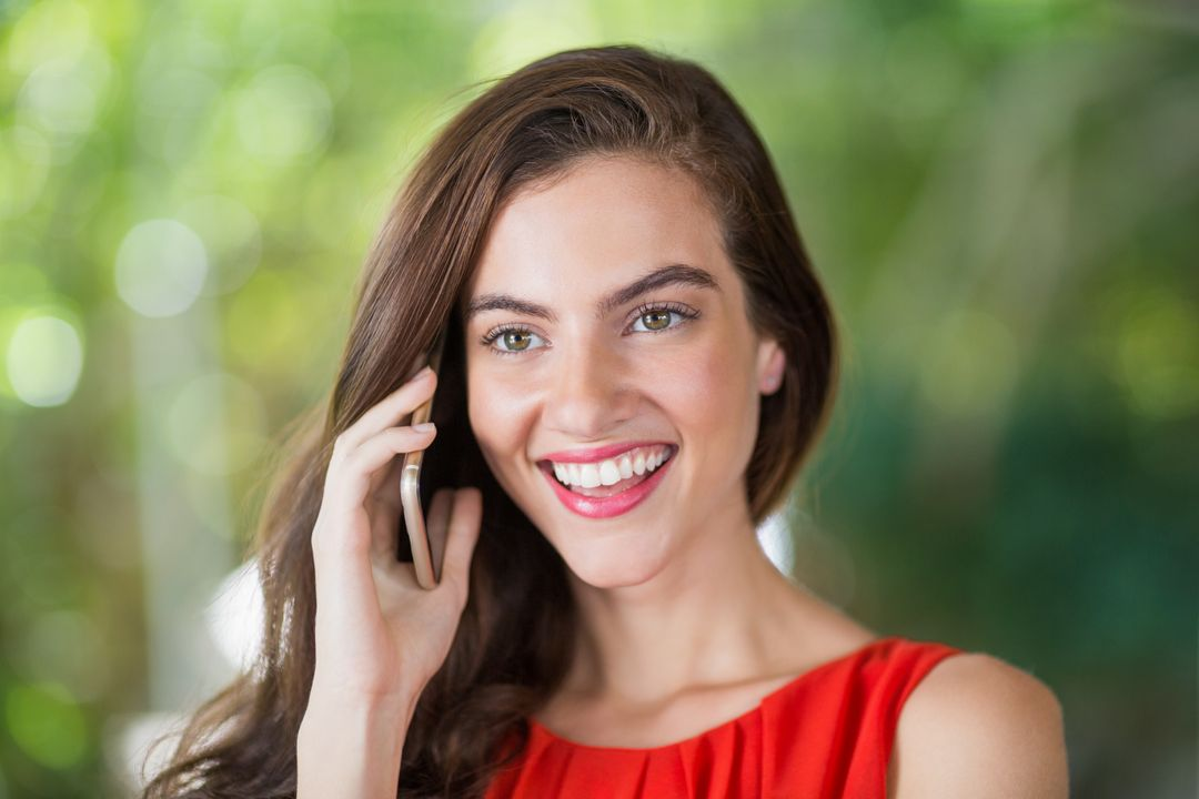 Beautiful woman smiling while talking on her mobile phone Free Stock Images from PikWizard