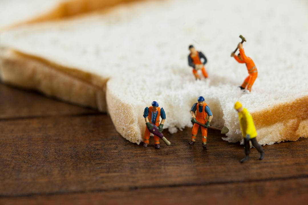 Conceptual image of miniature workers working on sliced of bread Free Stock Images from PikWizard
