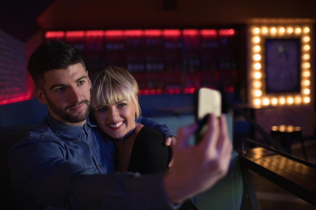 Smiling couple taking selfie on mobile phone in bar