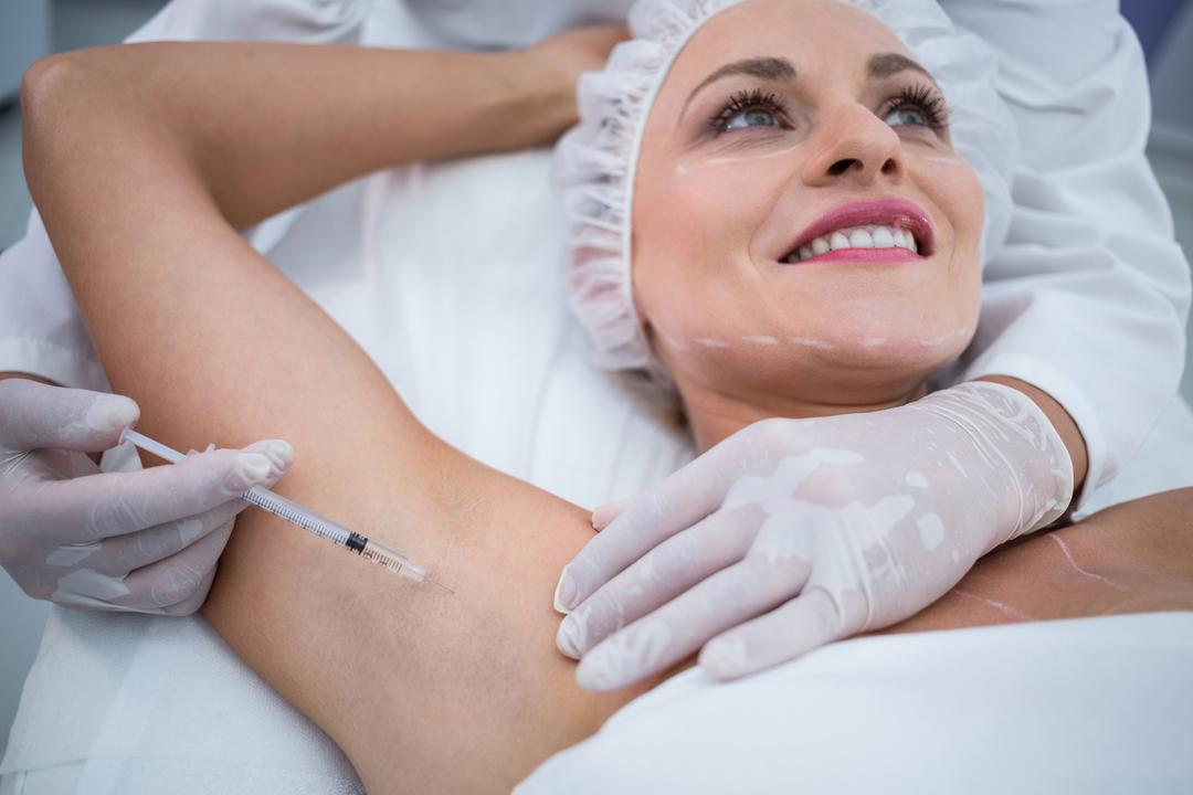 Close-up of doctor injecting woman on her arm pits