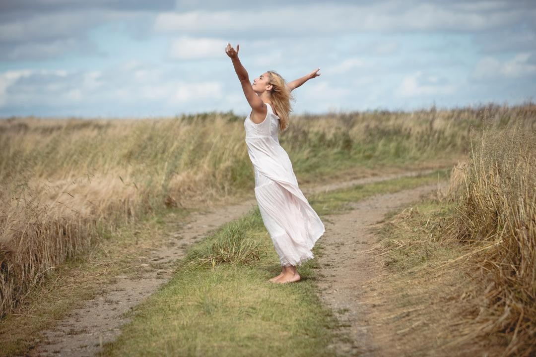 Carefree blonde woman standing on the field path with arms spread