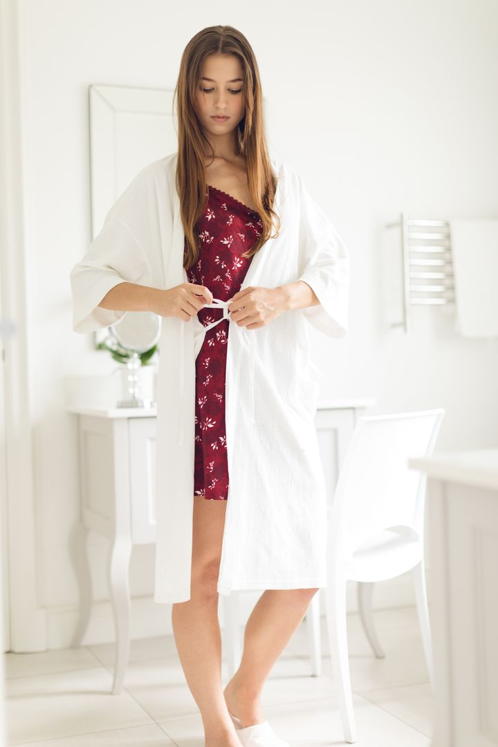 Beautiful woman tying up belt of bathrobe in bathroom at comfortable home
