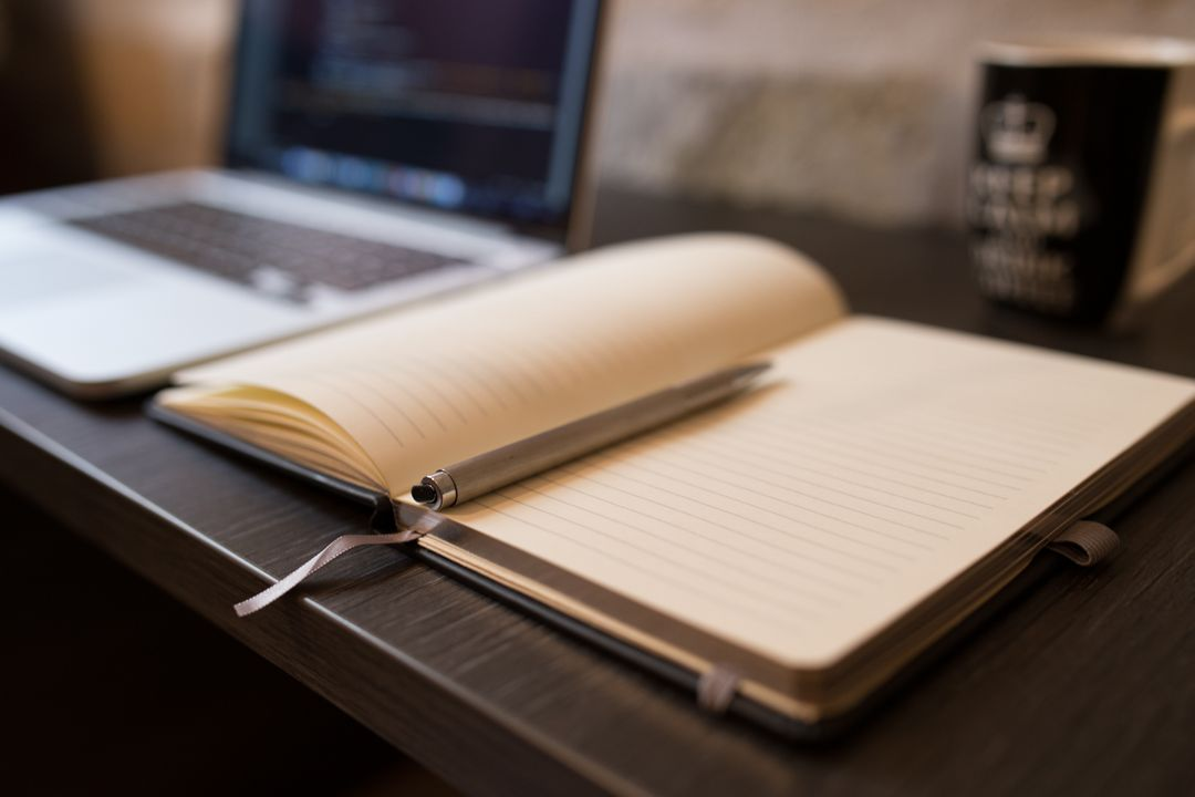 Image of a Notebook with a Pen on a Desk
