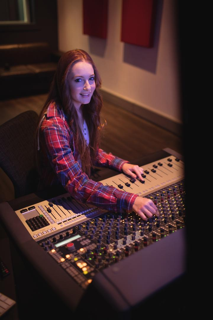 Portrait of female audio engineer using sound mixer in recording studio Free Stock Images from PikWizard