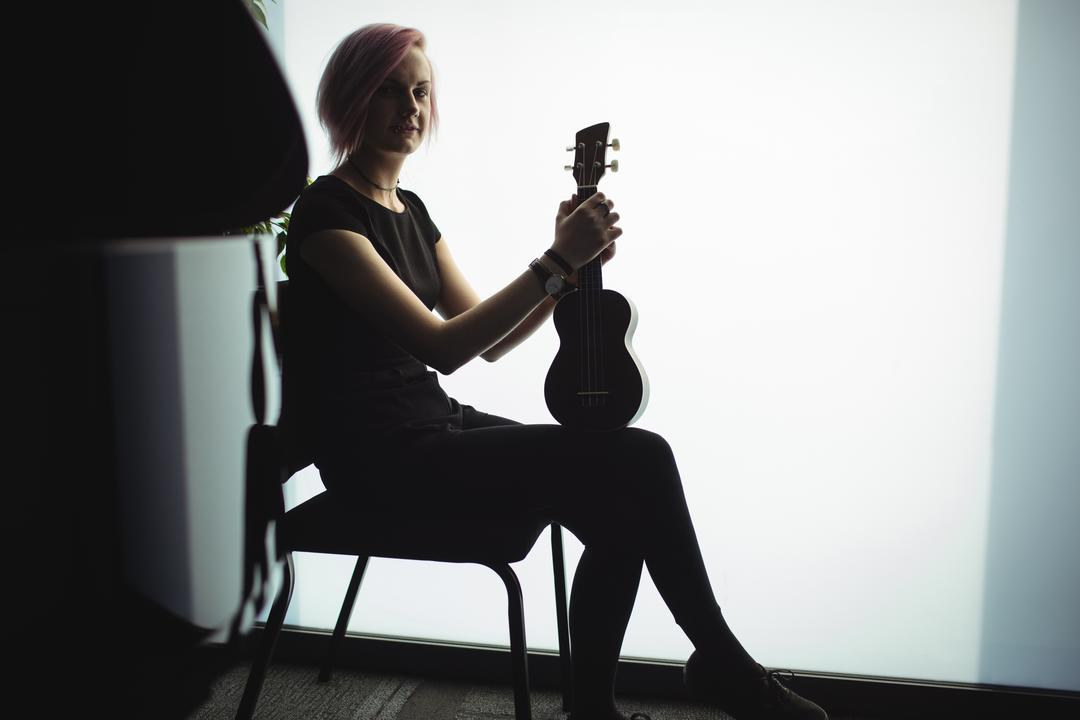 Portrait of woman sitting with a guitar in music school