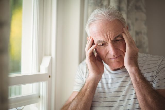 Stressed senior man standing by window