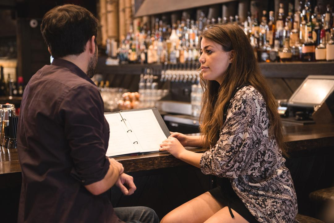 Couple discussing over menu at bar counter