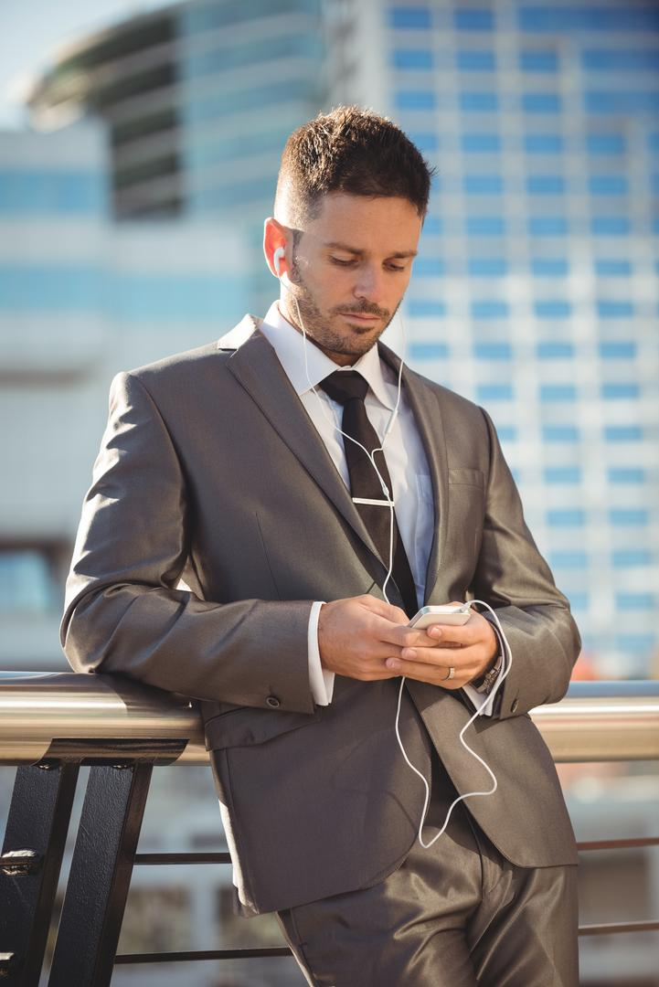 Businessman listening to music and using mobile phone near office building