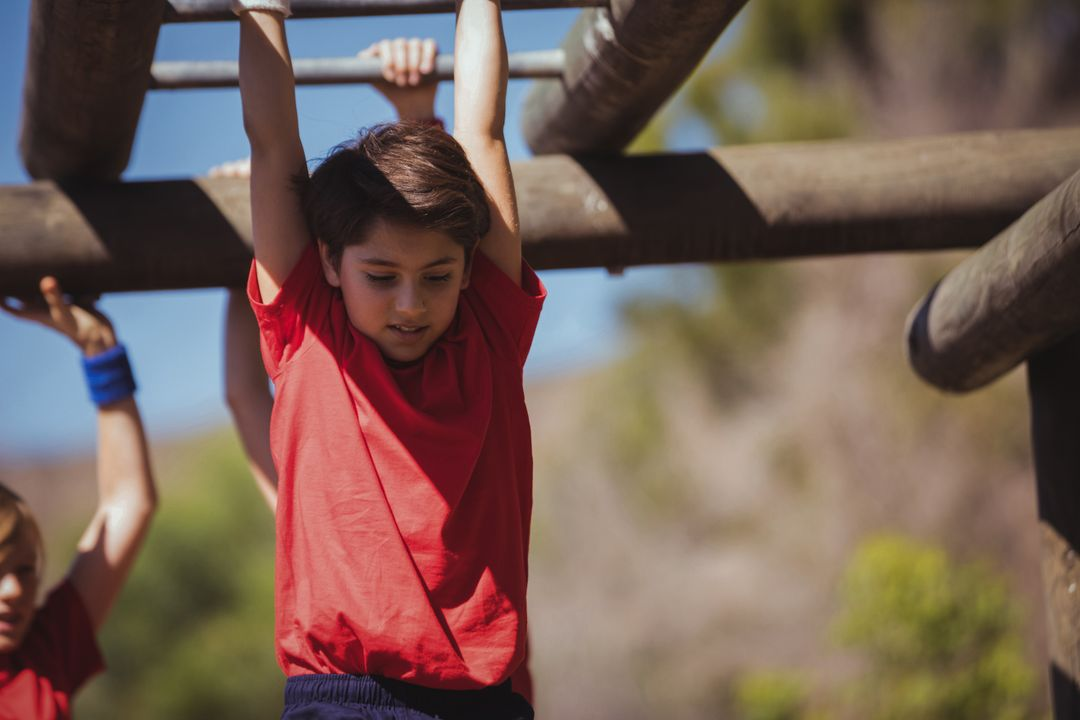Kids climbing monkey bars during obstacle course training in the boot camp Free Stock Images from PikWizard