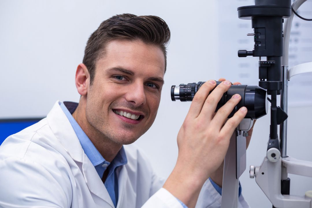 Smiling optometrist looking through biomicroscope in ophthalmology clinic