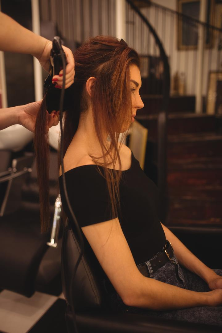 Woman is getting her hair straightened at hair saloon