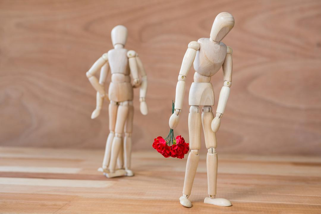 Conceptual image of figurine depressed with bunch of flowers walking away from couple Free Stock Images from PikWizard