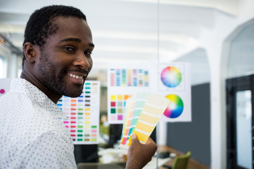 Male graphic designer holding color swatch in office Free Stock Images from PikWizard