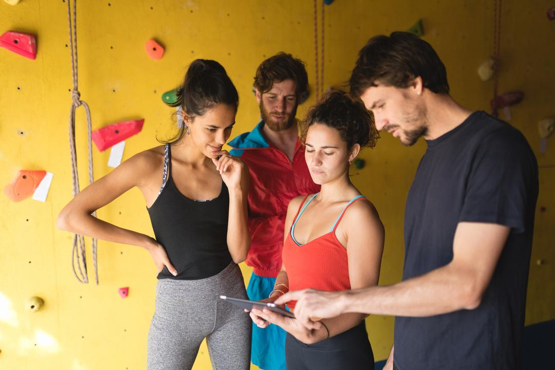 Friends using digital tablet while standing by climbing wall in gym