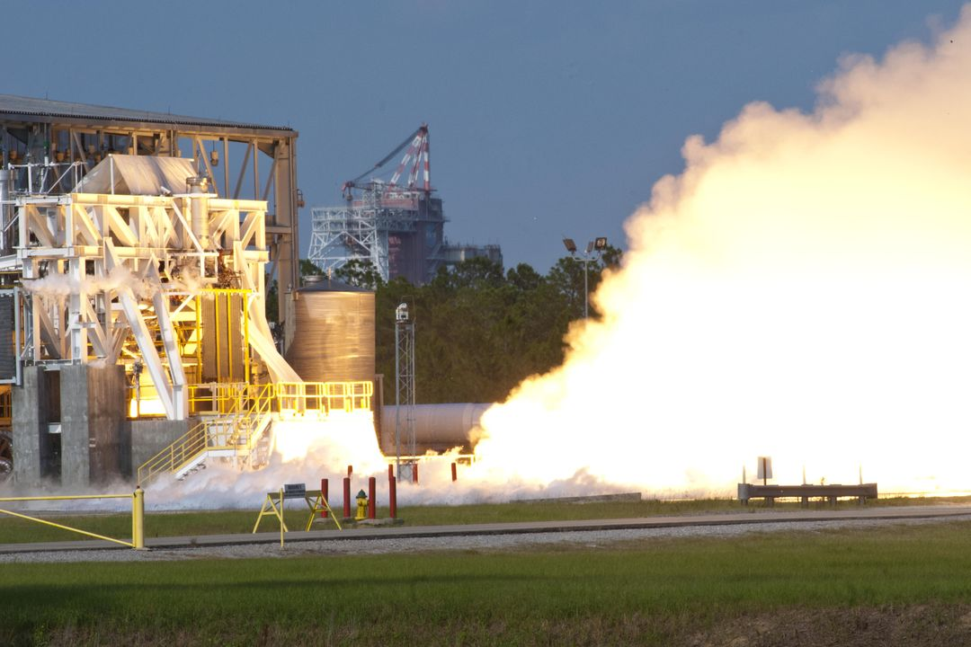 NASA engineers tested an Aerojet AJ26 rocket engine on the E-1 Test Stand at Stennis Space Center on June 25, 2012, against the backdrop of the B-1/B-2 Test Stand. The engine will be used by Orbital Sciences Corporation to power commercial cargo flights to the International Space Station.