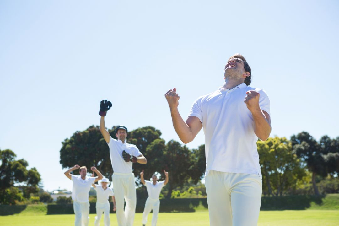 Happy cricket team enjoying victory while standing on field against clear sky Free Stock Images from PikWizard