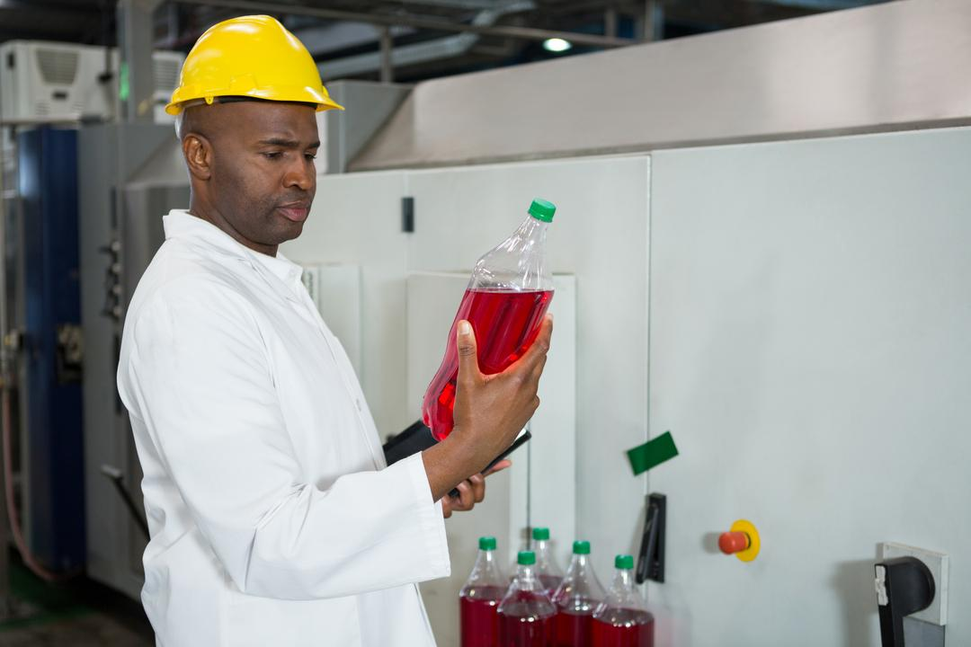Serious worker examining bottles in juice factory Free Stock Images from PikWizard