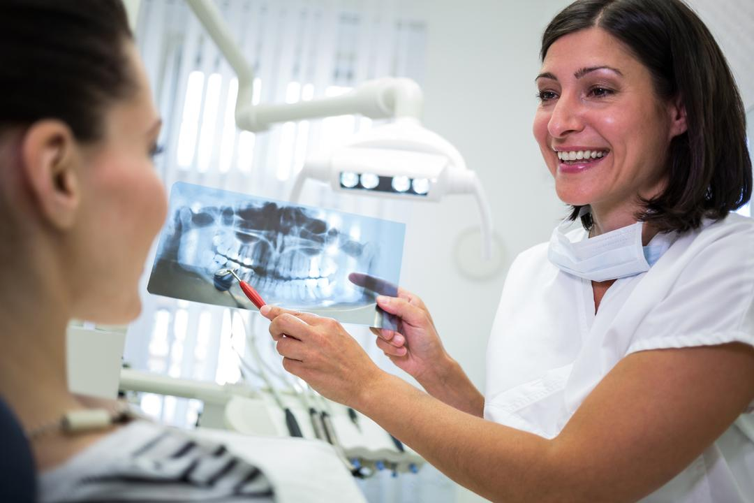 Dentist showing x-ray to her patient in dental clinic Free Stock Images from PikWizard