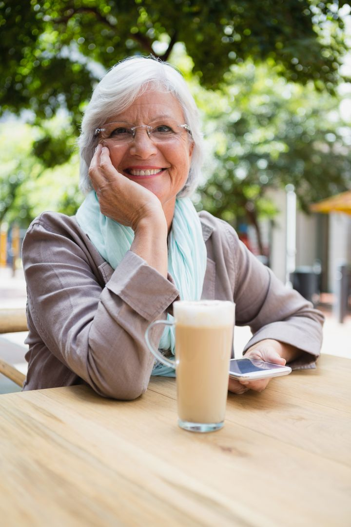 Portrait of senior woman holding mobile phone in outdoor café Free Stock Images from PikWizard