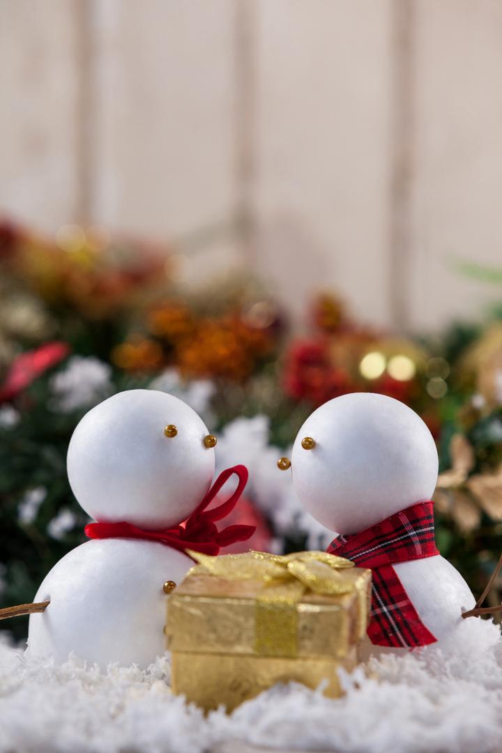 Close-up of two snowman with christmas gift