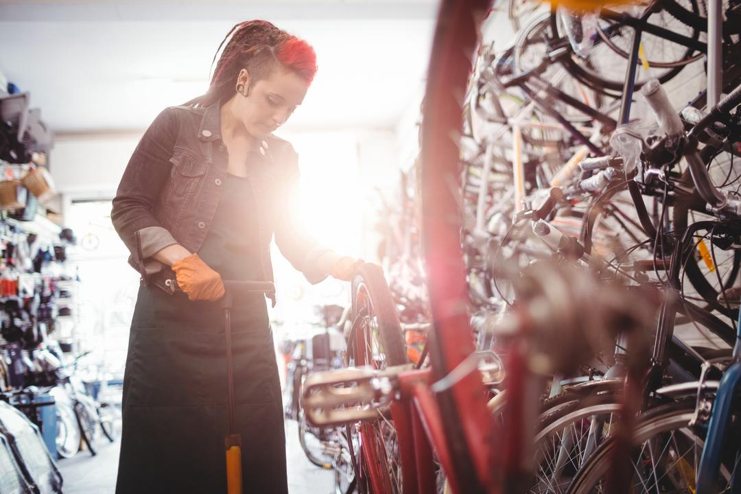Mechanic filling air into bicycle tire with air pump in workshop