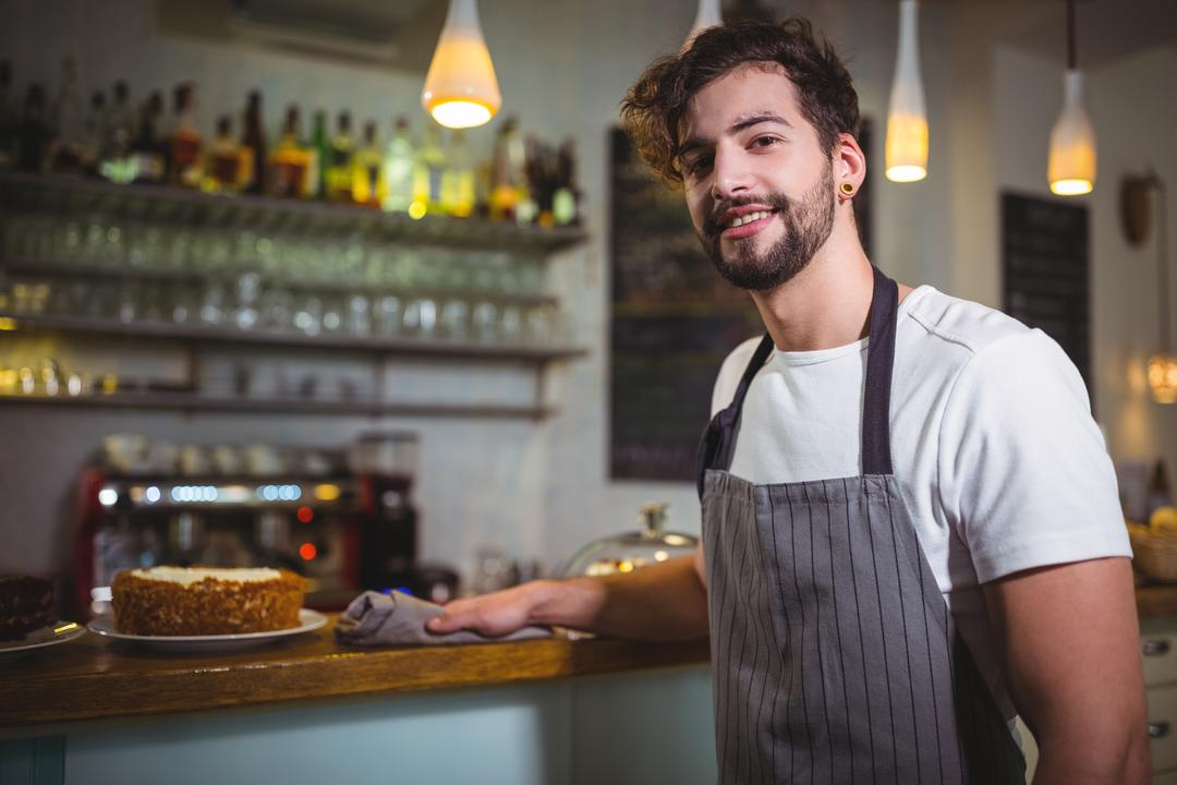 Portrait of smiling waiter wiping counter with napkin in café