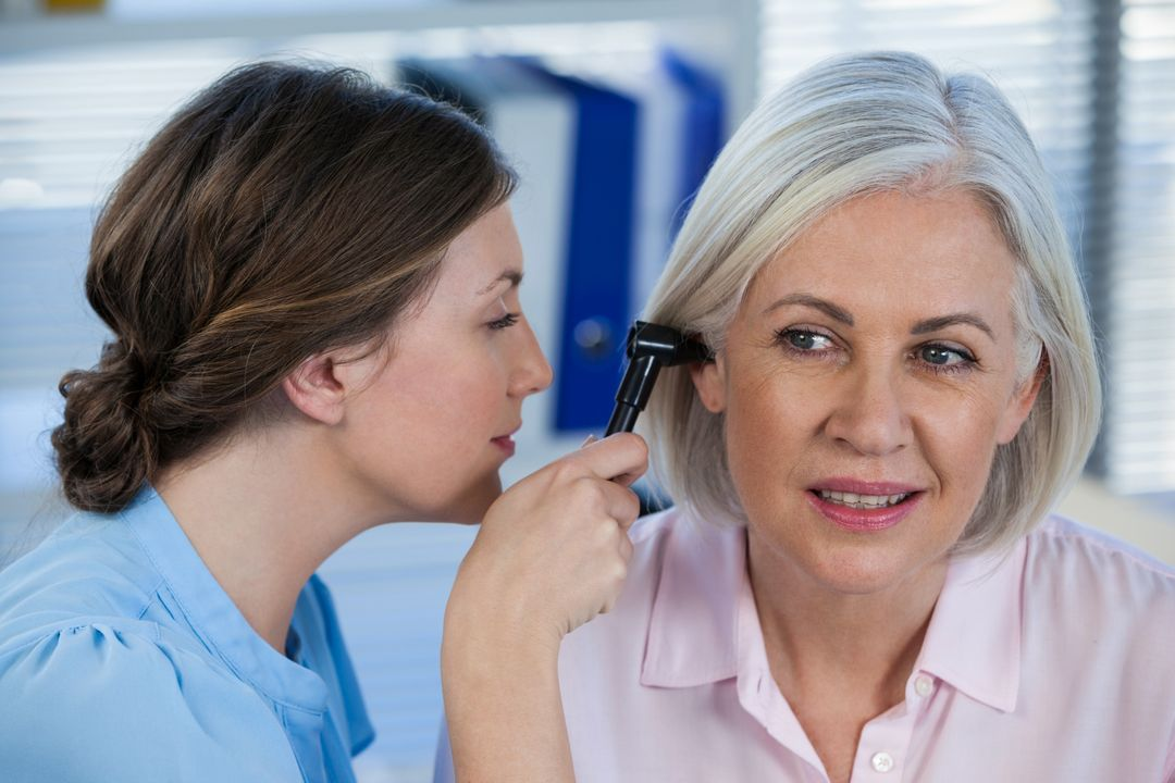 Doctor examining patients ear with otoscope in clinic Free Stock Images from PikWizard