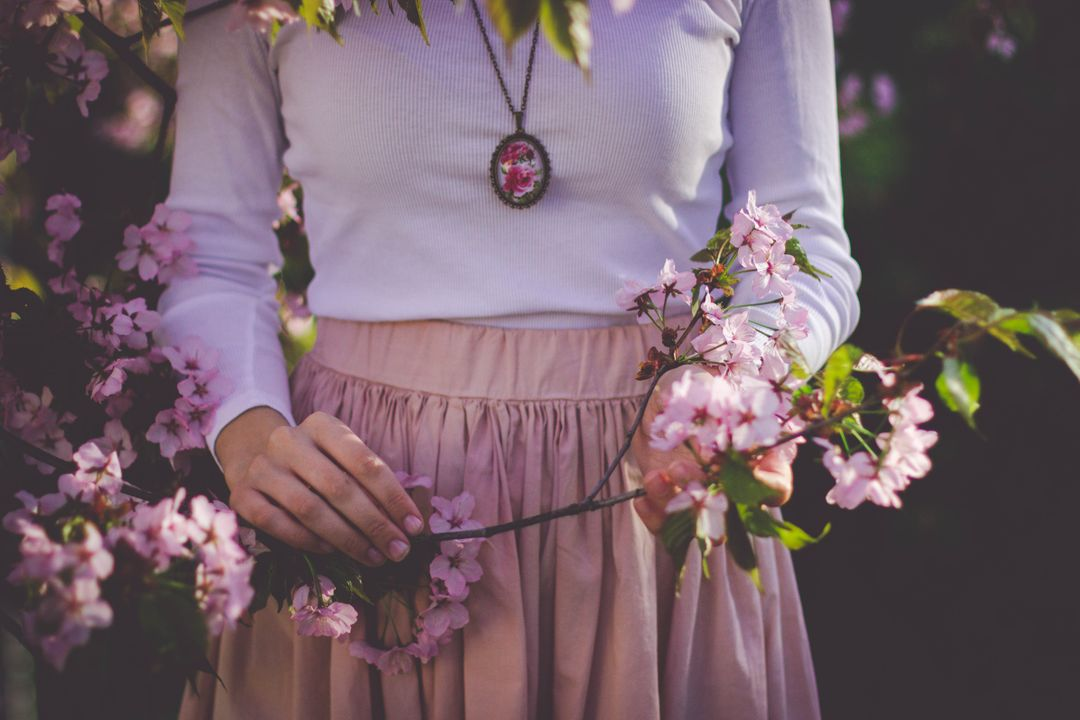 Image of woman holding pink flowers with green leaves
