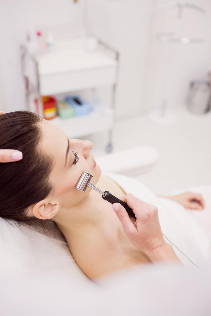 Dermatologist performing laser hair removal on patient face in clinic