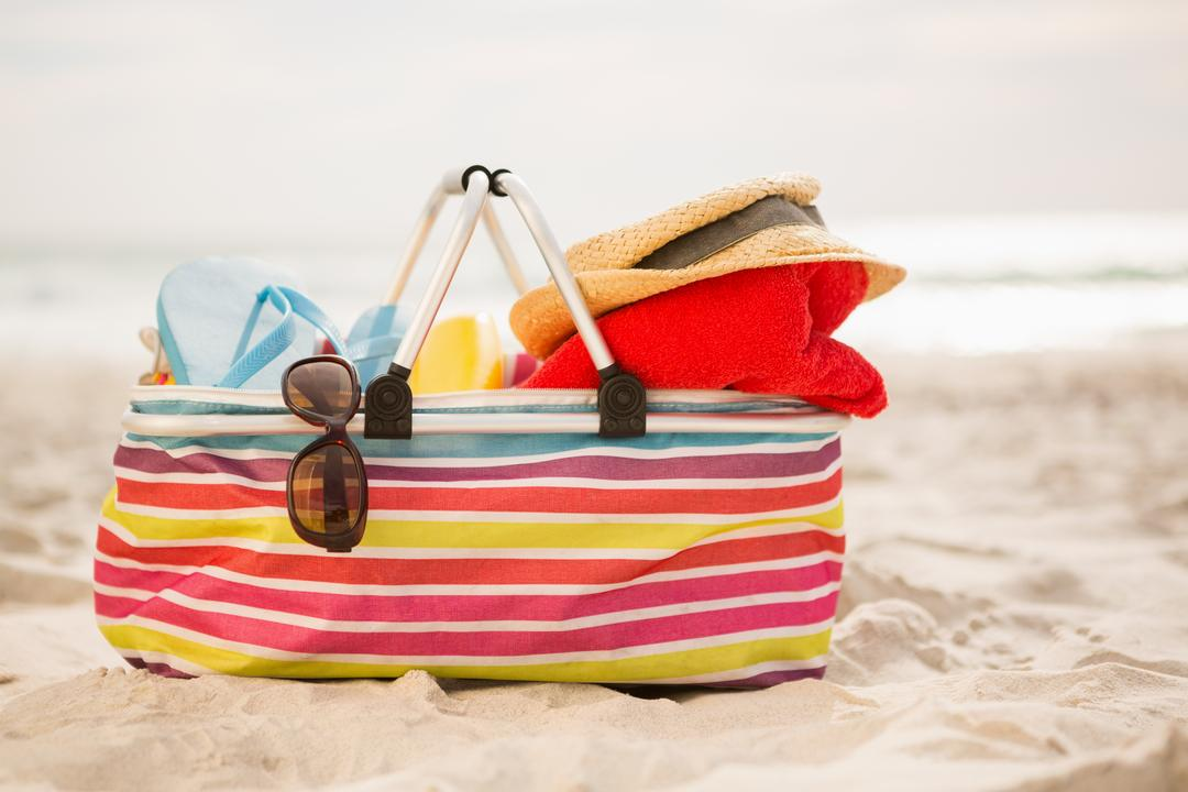 Bag with beach accessories kept on sand at beach