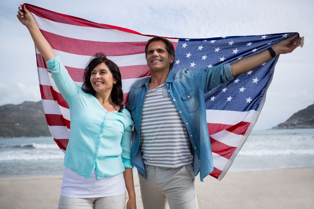 Couple holding american flag on beach during winter Free Stock Images from PikWizard