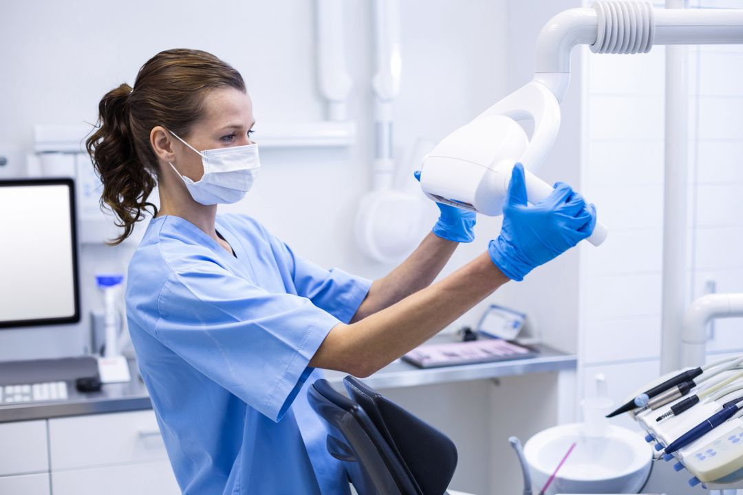 Dental assistant adjusting light in dental clinic Free Stock Images from PikWizard