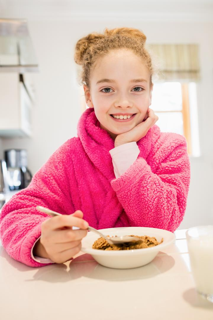 Cute girl in bathrobe having breakfast in kitchen at home