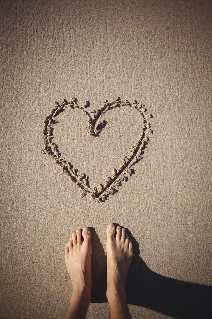 Low section of woman standing near heart drawn on the beach Free Stock Images from PikWizard