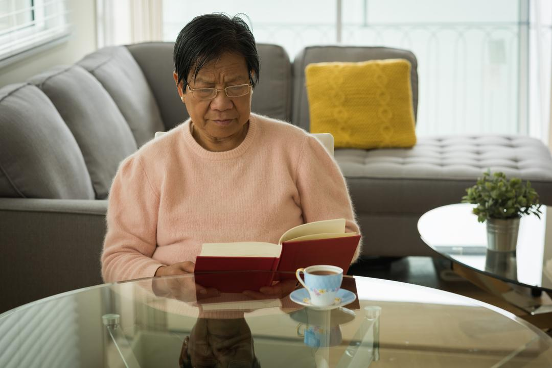 Senior woman reading book at table in living room