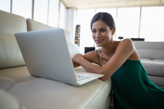 Young businesswoman using laptop on sofa at office