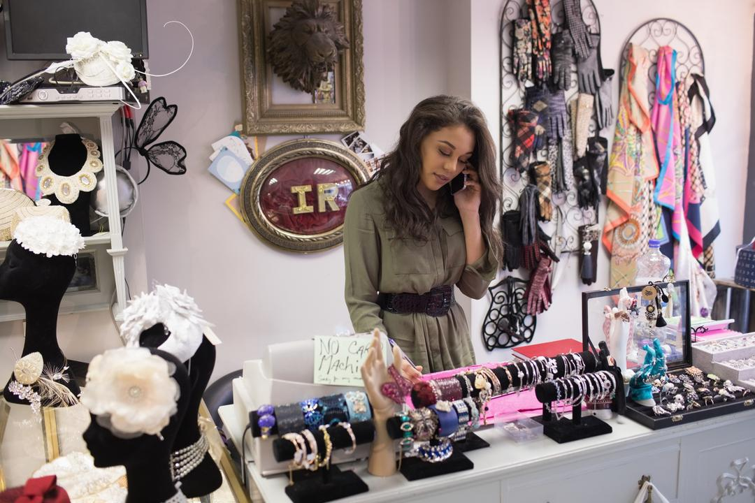 Woman selecting bangles in jewelry section of boutique