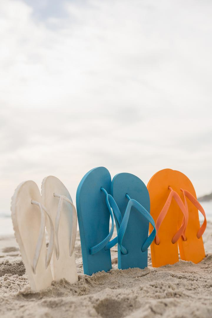 Multi-color flip flops arranged in a row in sand at beach