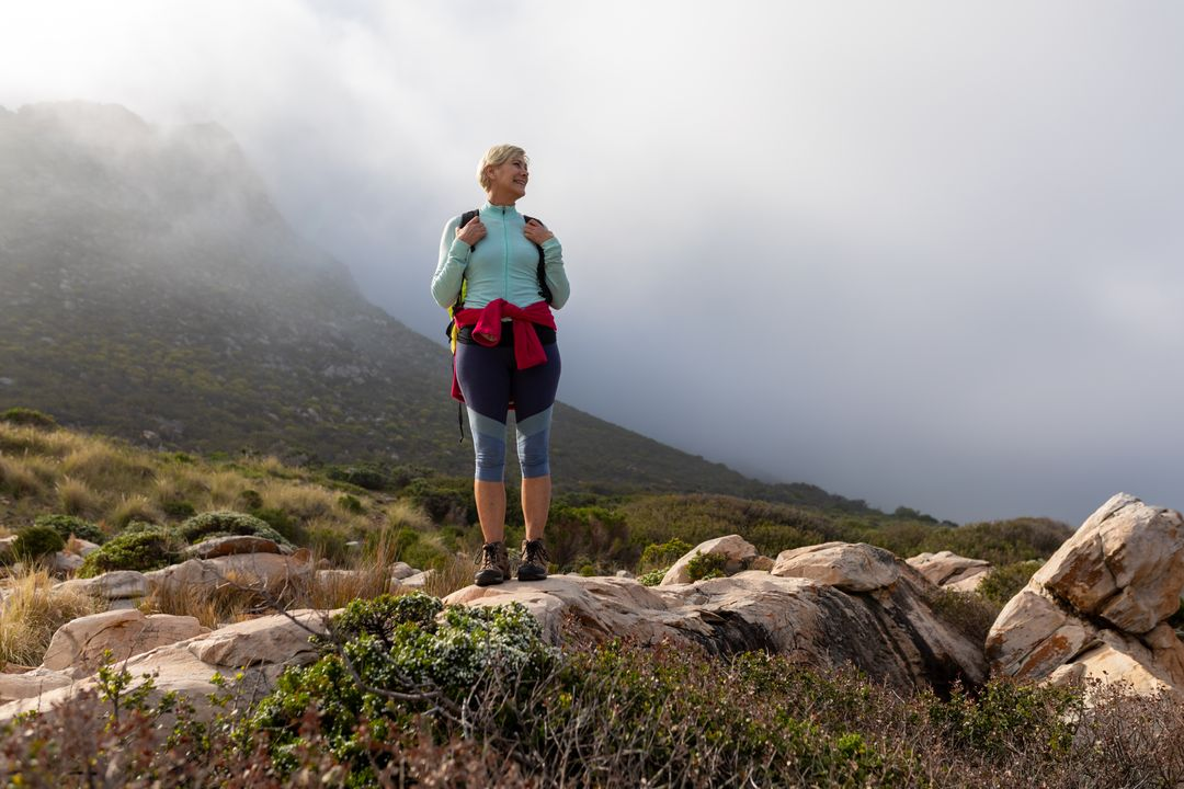 Caucasian hiker senior woman with backpack standing on the rock while trekking in the mountains. Trekking hiking and adventure concept. Free Stock Images from PikWizard