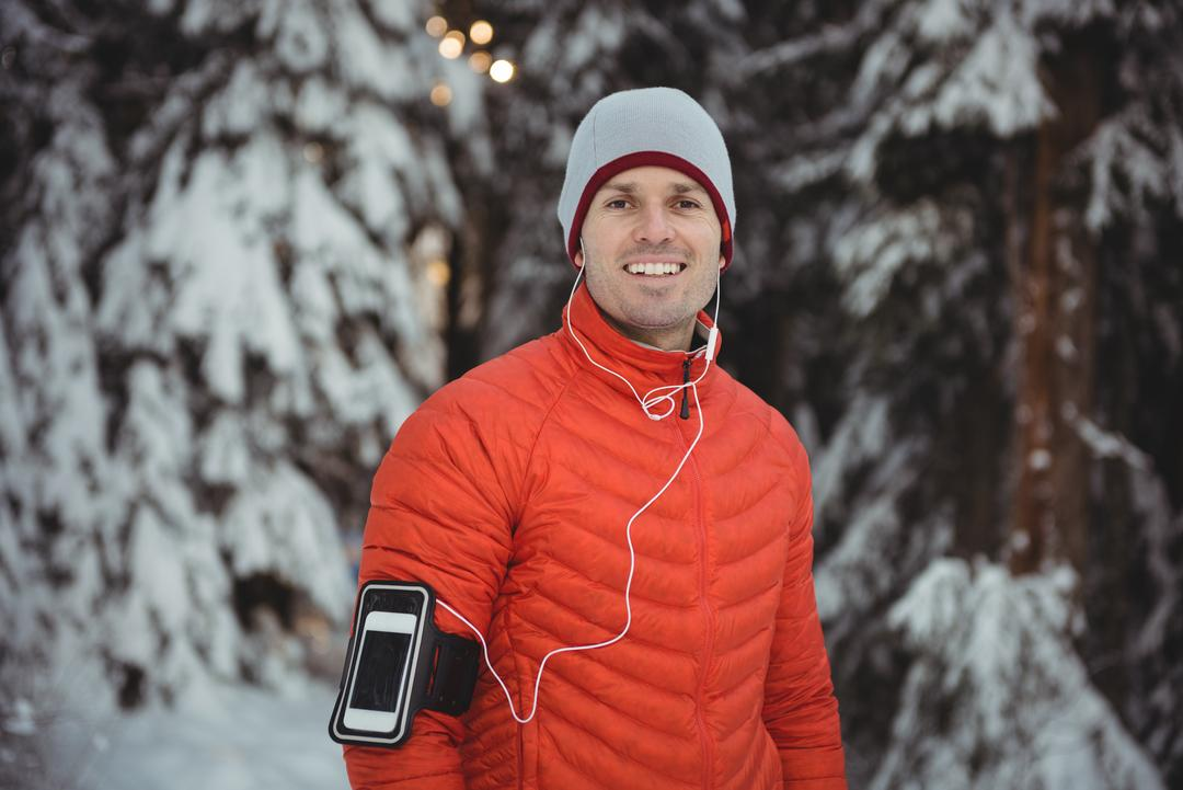 Portrait of man listening to music in headphones from smart phone during winter