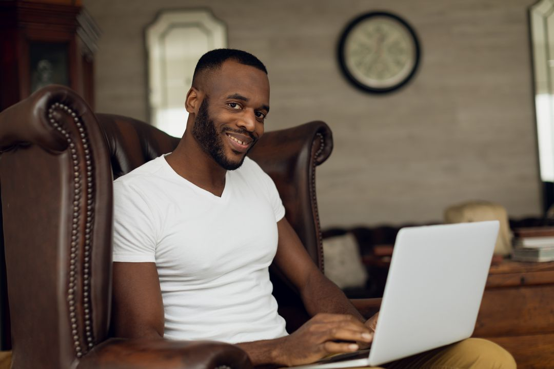 Digital composite of an African-American smiling and sitting on a leather chair inside a room while using a laptop