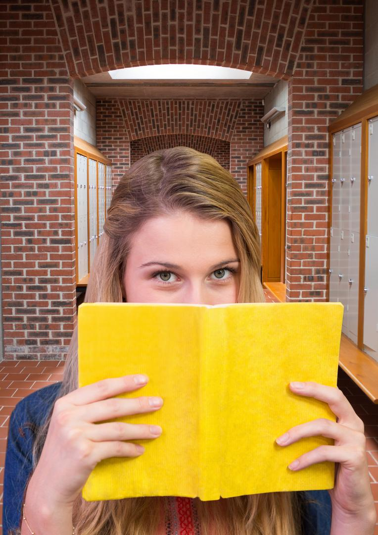 Digital composite image of teenage student hiding her face behind book in locker room