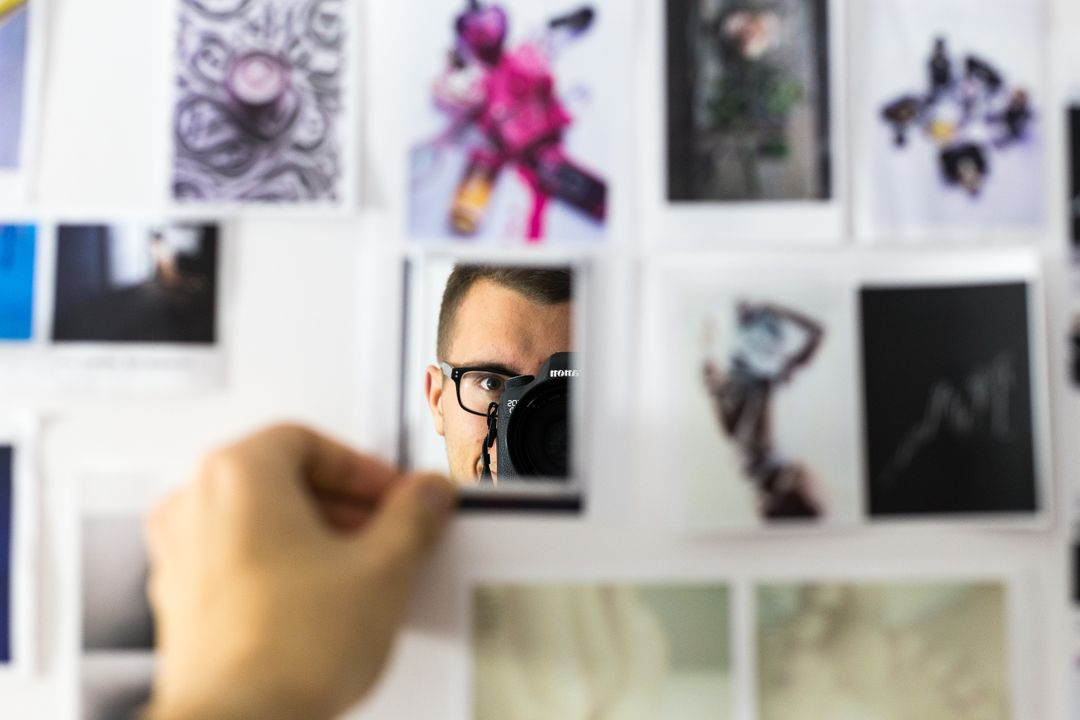 Man taking photo in a mirror surrounded by a collage of images
