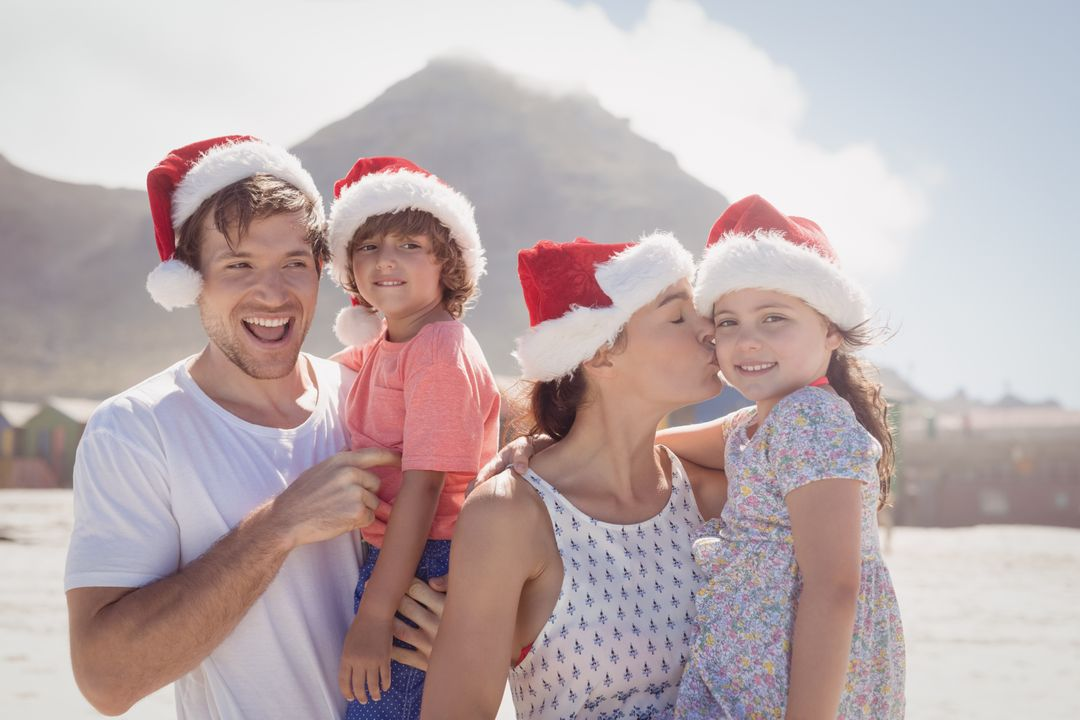 Cheerful family wearing Santa hat during sunny day at beach