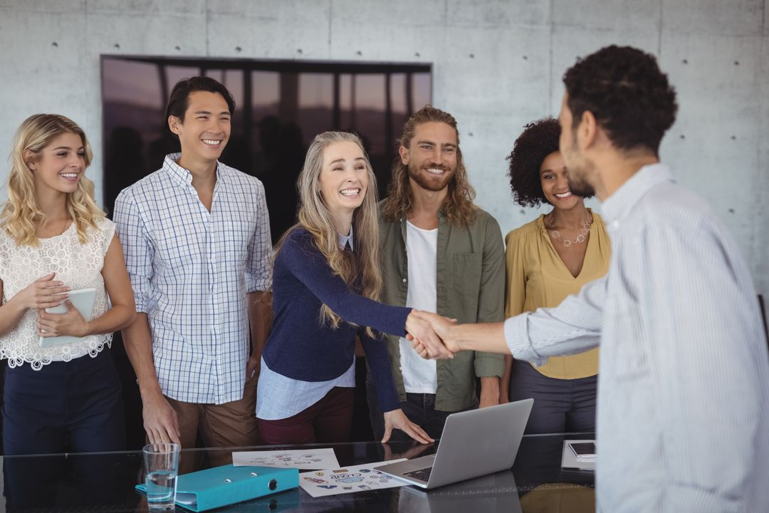 Smiling young business people shaking hands at desk in creative office