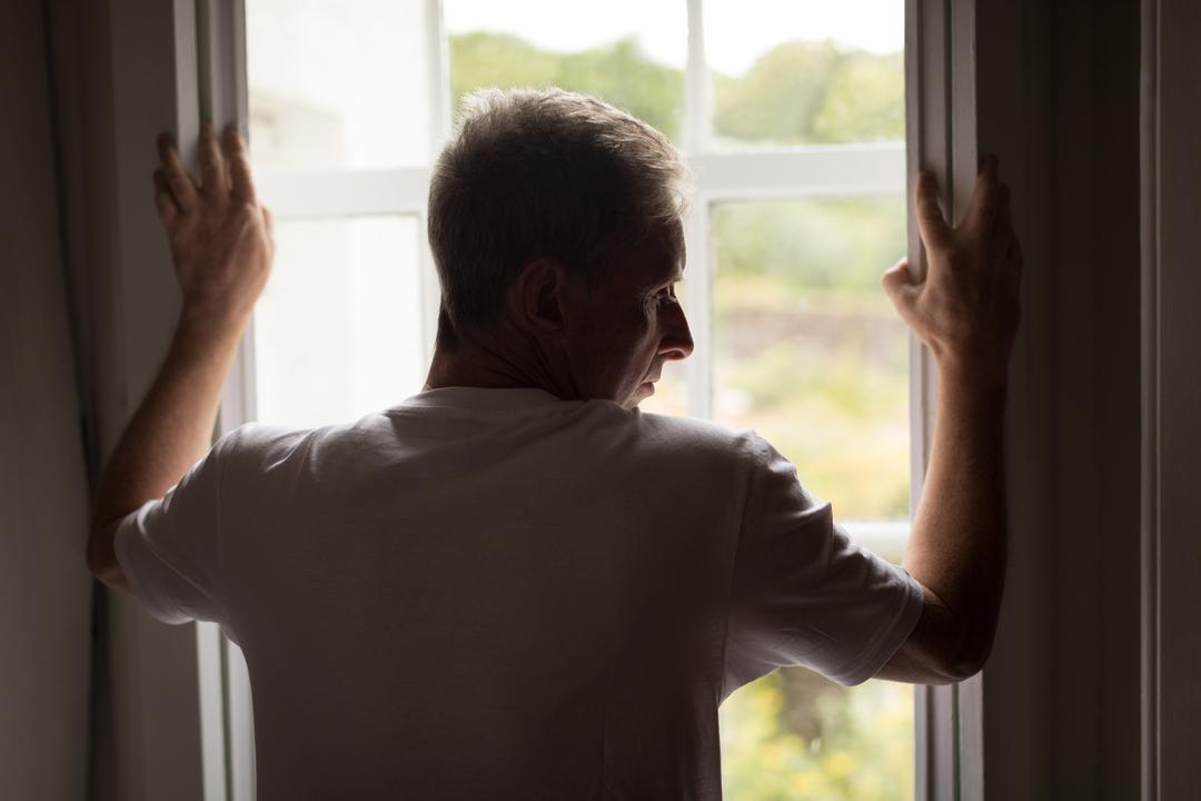Thoughtful senior man standing near window at home
