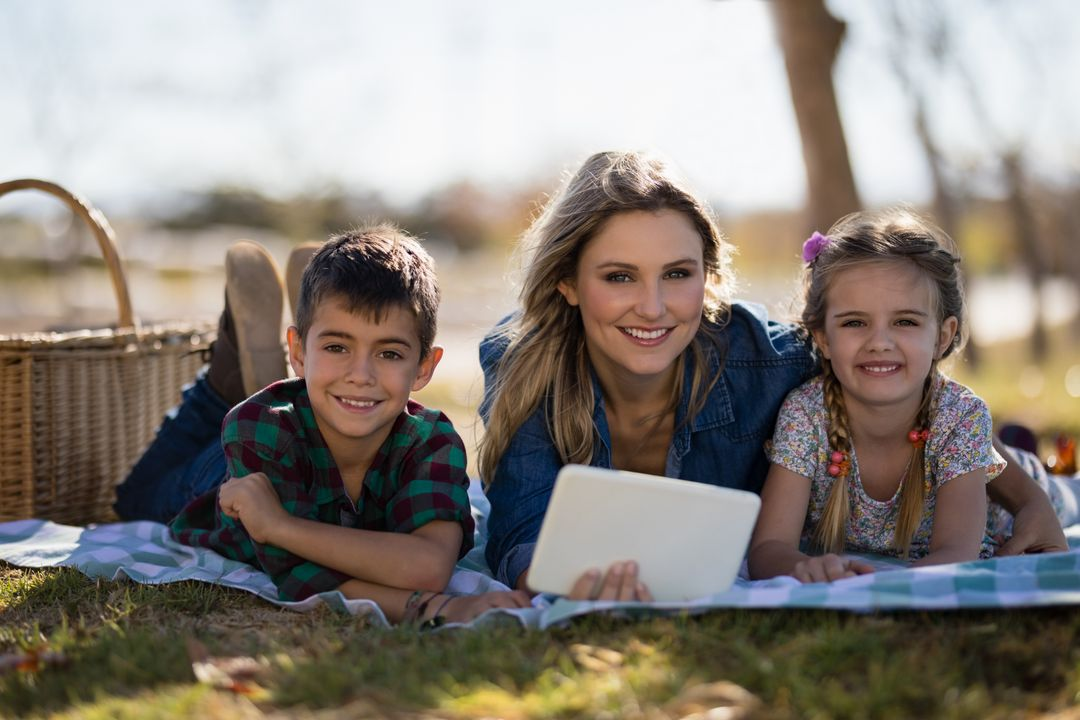 Portrait of happy mother and kids holding digital tablet in park